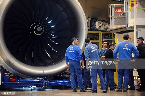 This photo taken on March 26 shows technicians looking at a RollsRoyce made jet engine provided by UTC Aerospace Systems as they work on an A350900...