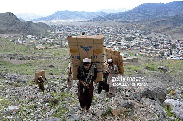 This photo taken on March 28 2015 shows young Pakistani labourers near the Torkham border crossing as they carry vehicle parts on their backs to...