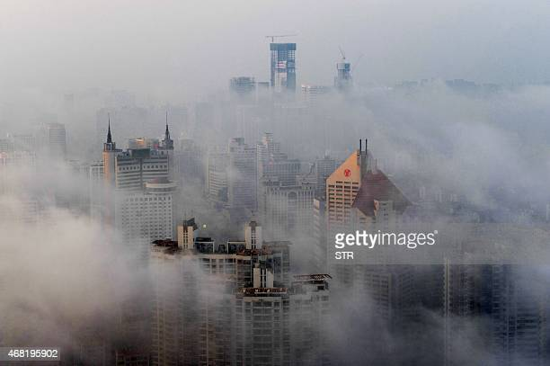 This photo taken on March 29 2015 shows heavy fog covering buildings in Qingdao east China's Shandong province Falls in Chinese housing prices...