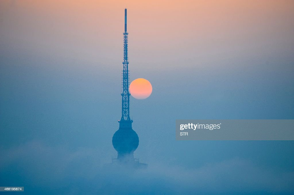 This photo taken on March 29 2015 shows the top of a tower looming out of heavy fog in Qingdao east China's Shandong province Falls in Chinese...