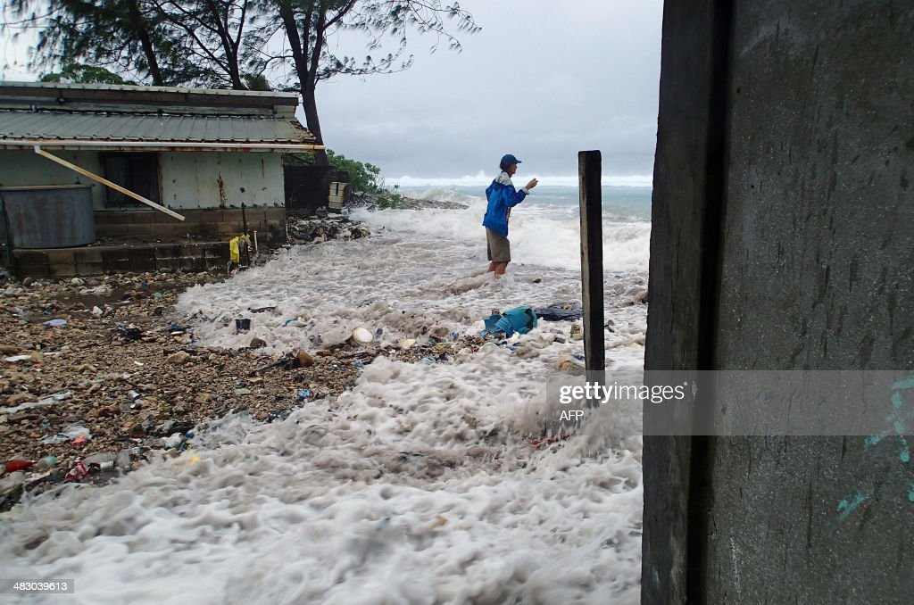 This photo taken on March 3 2014 shows a resident surrounded by the onrushing high tide energized by a storm surge that damaged a number of homes...