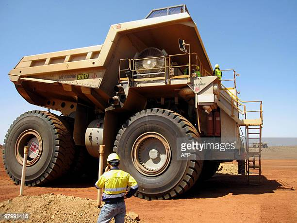 This photo taken on March 5 2010 shows Sino Iron worker Darrell Lim in front of a massive dump truck at Citic Pacific Mining's Sino Iron magnetite...