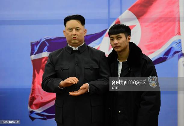 This photo taken on March 6 2017 shows a Chinese visitor posing for photos next to a wax figure of North Korean leader Kim JongUn in Shenyang...
