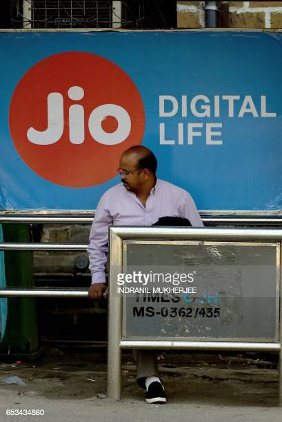 This photo taken on March 7 2017 shows an Indian man sitting in front of a sign for Indian mobile service provider Jio at a bus stop in Mumbai...
