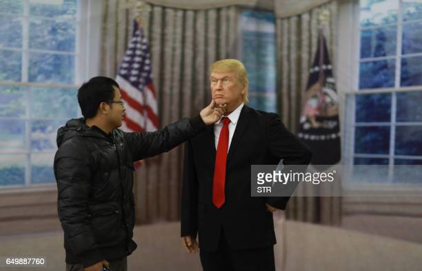 This photo taken on March 8 2017 shows a Chinese visitor touching a wax figure of US President Donald Trump in Shenyang northeastern China's Liaoning...