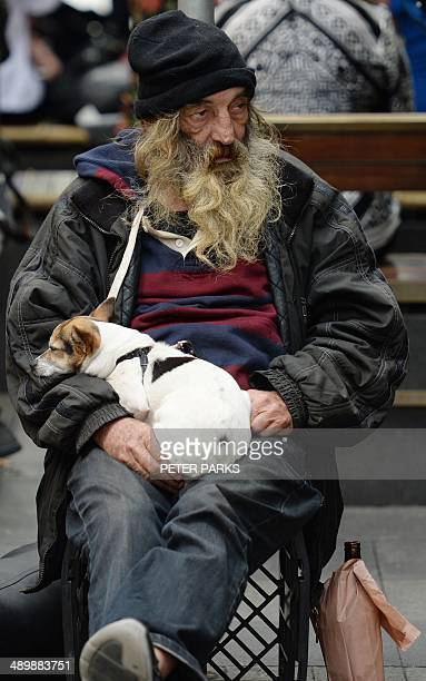 This photo taken on May 12 2014 shows a homeless man sitting with his dog on a street in Sydney Australian Prime Tony Abbott worked May 13 2014 to...