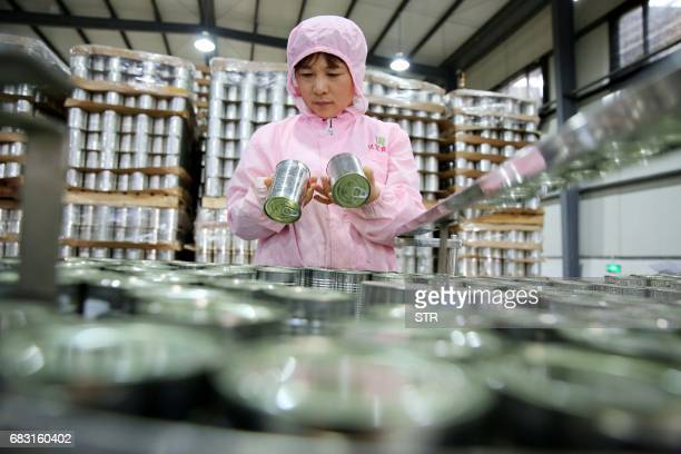 This photo taken on May 13 2017 shows a worker checking cans of asparagus at a food processing plant in Huaibei in China's Anhui province Products...