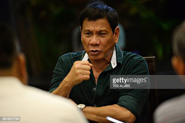 This photo taken on May 15 2016 shows Philippines' presidentelect Rodrigo Duterte gesturing as he talks with military and police officials during an...