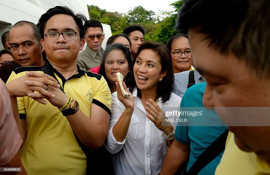 This photo taken on May 15, 2016 shows vice-presidential candidate and activist lawyer-turned congresswoman Leni Robredo interacting with supporters after attending a mass at the Church of Gesu at the Ateneo de Manila University in Manila. The son and namesake of the late Philippine dictator Ferdinand Marcos has narrowly lost the election for vice president to political neophyte Leni Robredo, according to an official count that was only completed on May 27, almost three weeks after polls closed. / AFP / NOEL