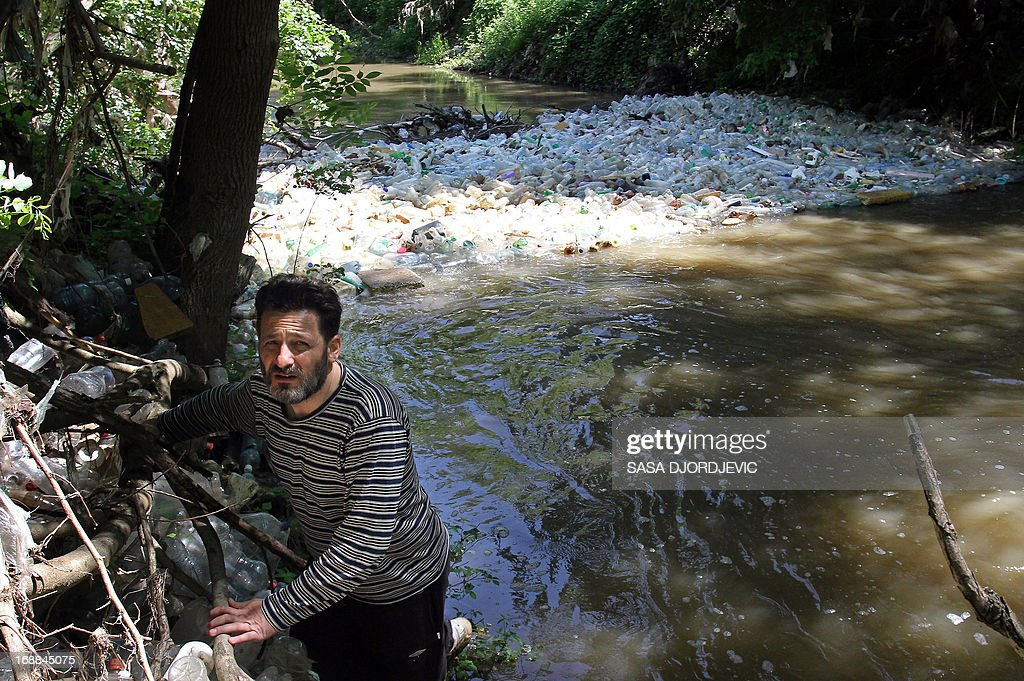 This photo taken on May 15, 2013, shows Serbian amateur ecologist Srboljub Pesic examining the South Morava river filled with discarded plastic bottles and other garbage, near the town of Vranje.
