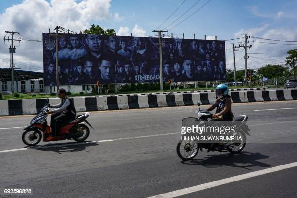 This photo taken on May 17 2017 shows 58yearold former Thai MP Newin Chidchob and Buriram United football players pictured on a giant billboard in...