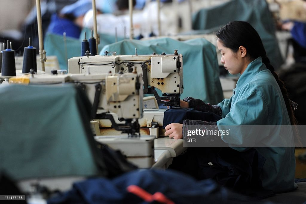 This photo taken on May 19 2015 shows a worker producing clothes in a factory in Huaibei east China's Anhui province China's manufacturing activity...
