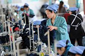 This photo taken on May 19 2015 shows workers producing clothes in a factory in Huaibei east China's Anhui province China's manufacturing activity...