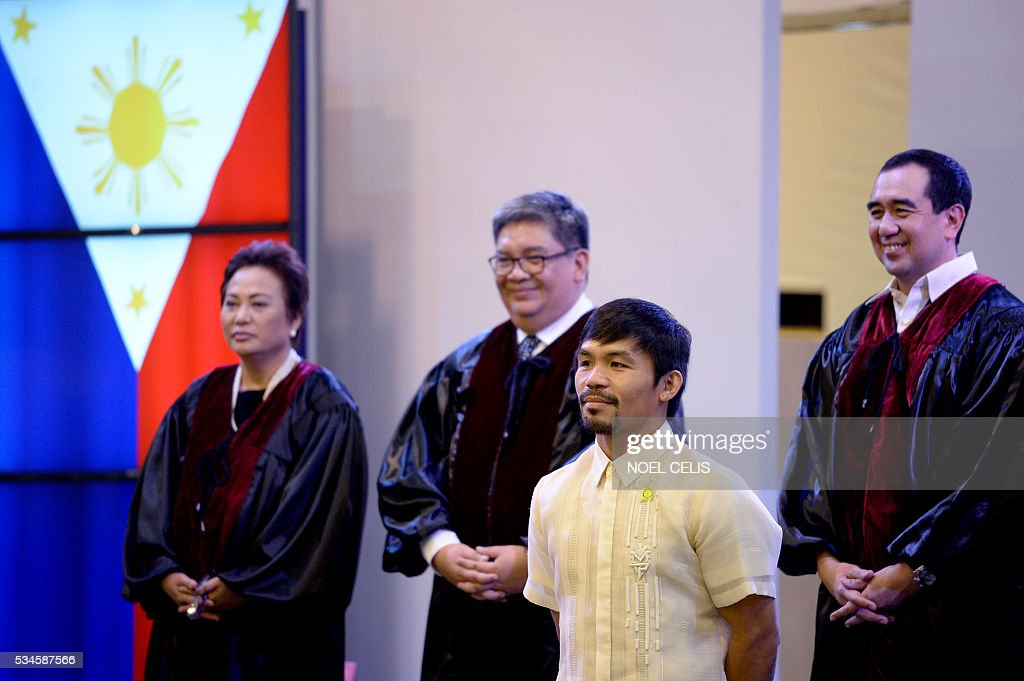 This photo taken on May 19, 2016, shows Philippine boxing icon and newly elected Senator Manny Pacquiao attending the Commission on Elections (COMELEC) proclamation of senators at the Philippine International Convention Center (PICC) in Manila Boxing legend Manny Pacquiao is giving the Rio Olympics a miss as he tries to make good on his promise to be a full-time politician. Pacquiao, a newly proclaimed senator in the Philippines, said Friday that he was declining an invitation to compete in the Olympics in August to focus on being a top lawmaker. / AFP / NOEL