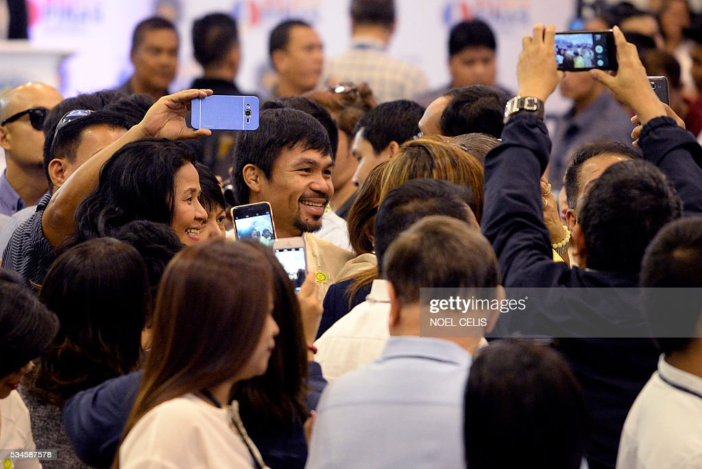 This photo taken on May 19, 2016, shows Philippine boxing icon and newly elected Senator Manny Pacquiao being surrounded by supporters at the Commission on Elections (COMELEC) proclamation of senators at the Philippine International Convention Center (PICC) in Manila. Boxing legend Manny Pacquiao is giving the Rio Olympics a miss as he tries to make good on his promise to be a full-time politician. Pacquiao, a newly proclaimed senator in the Philippines, said Friday that he was declining an invitation to compete in the Olympics in August to focus on being a top lawmaker. / AFP / NOEL