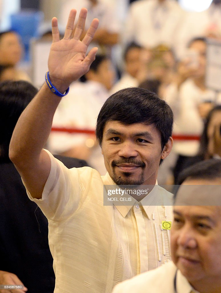 This photo taken on May 19, 2016, shows Philippine boxing icon and newly elected Senator Manny Pacquiao waving to the photographers at the Commission on Elections (COMELEC) proclamation of senators at the Philippine International Convention Center (PICC) in Manila. Boxing legend Manny Pacquiao is giving the Rio Olympics a miss as he tries to make good on his promise to be a full-time politician. Pacquiao, a newly proclaimed senator in the Philippines, said Friday that he was declining an invitation to compete in the Olympics in August to focus on being a top lawmaker. / AFP / NOEL