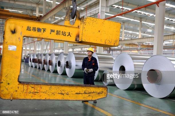 This photo taken on May 20 2017 shows a Chinese worker loading aluminium tapes at an aluminium production plant in Huaibei east China's Anhui...