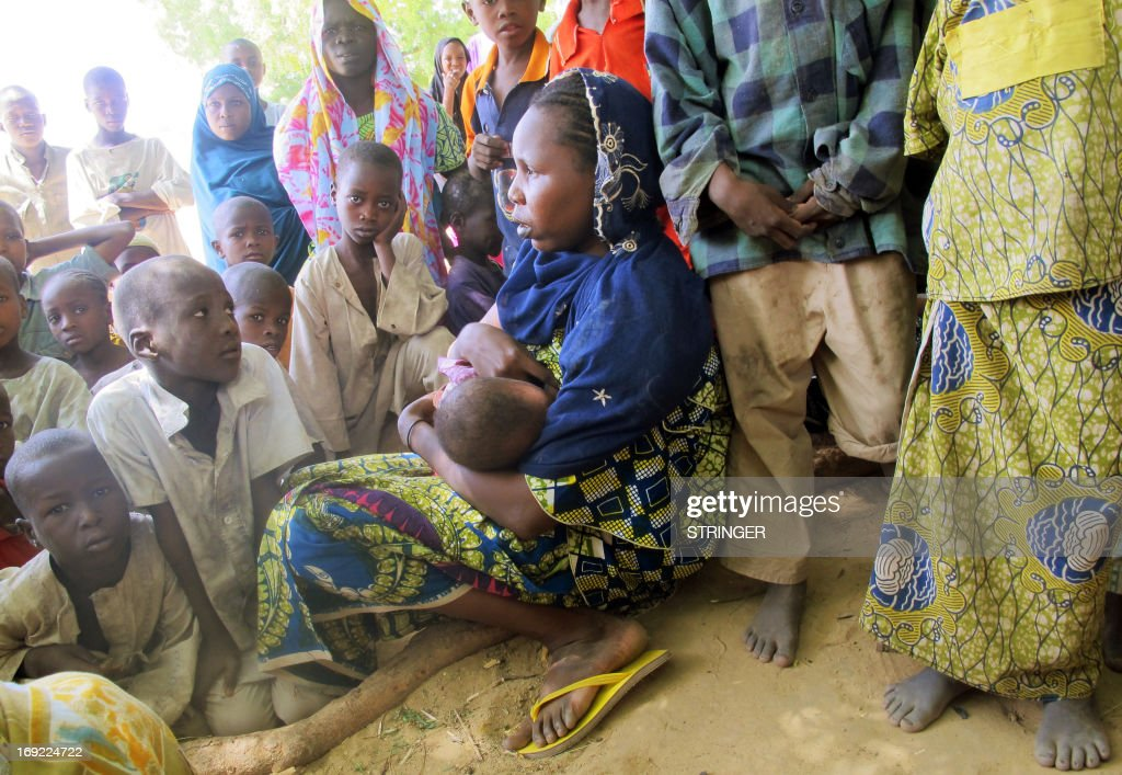 This photo taken on May 20, 2013, shows a Nigerian refugee mother breast-feeding her child as she sits amongst other refugees in the Cameroon village of Mainari. Several thousand Nigerian refugees have fled their country since the launch last week of an offensive by the Nigerian army against Islamist militant groups which have spread havoc in the region. On May 21 the Cameroon government declared that it would oppose the arrival of more Nigerian refugees on its soil.