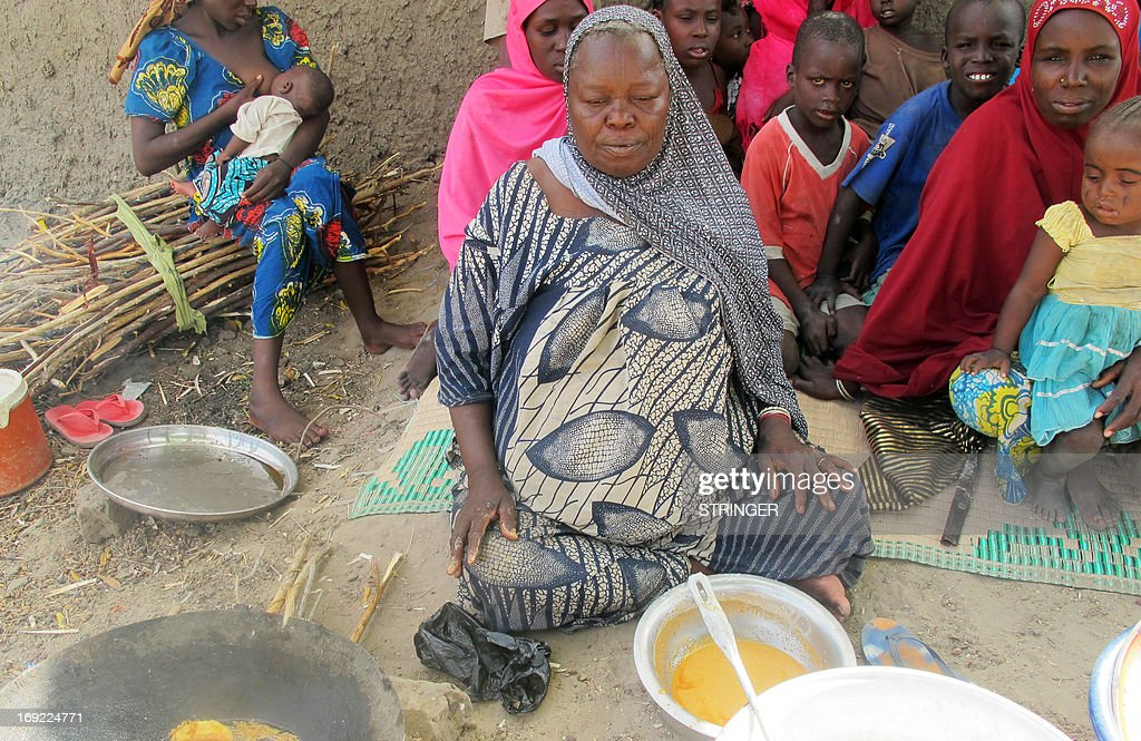 This photo taken on May 20, 2013, shows a Nigerian refugee woman preparing food as she sits amongst other refugees in the Cameroon village of Mainari. Several thousand Nigerian refugees have fled their country since the launch last week of an offensive by the Nigerian army against Islamist militant groups which have spread havoc in the region. On May 21 the Cameroon government declared that it would oppose the arrival of more Nigerian refugees on its soil. AFP PHOTO / STRINGER