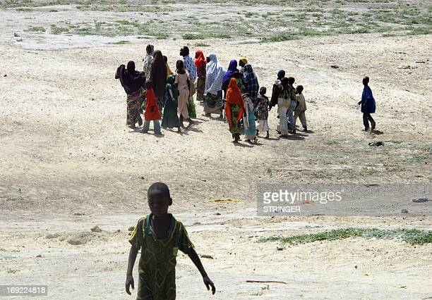 This photo taken on May 20 shows Nigerian refugee families walking in the Cameroon village of Mainari after fleeing violence in their country Several...