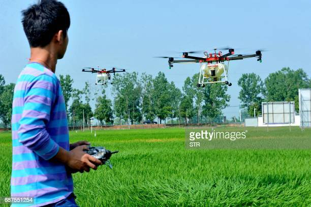 This photo taken on May 22 2017 shows Chinese villagers using an agricultural drone to spray pesticide on crops in a village in Poyang central...