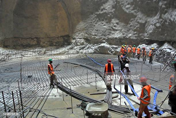 This photo taken on May 22 shows workers at the bottom of a chute at the controversial Gibe III dam under construction in Ethiopia's Omo valley The...