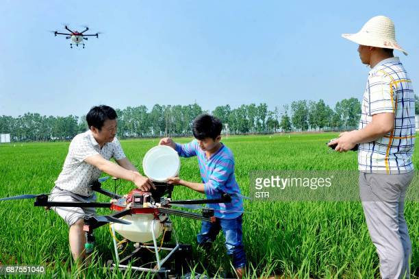 This photo taken on May 23 2017 shows Chinese villagers using an agricultural drone to spray pesticide on crops in a village in Poyang central...