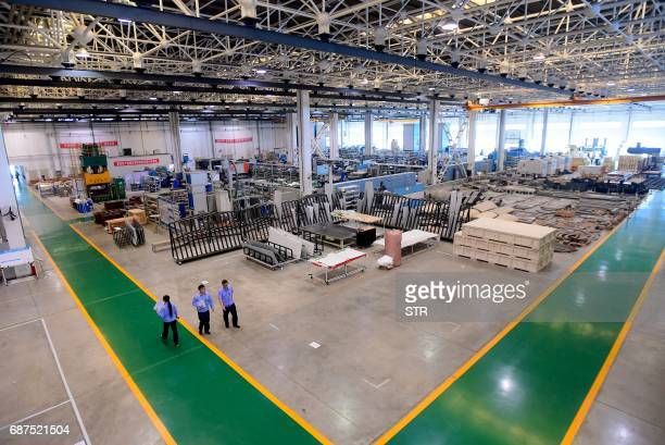 This photo taken on May 23 2017 shows Chinese workers walking at an assembly plant of Bombardier Q400 plane in Shenyang northeast China's Liaoning...