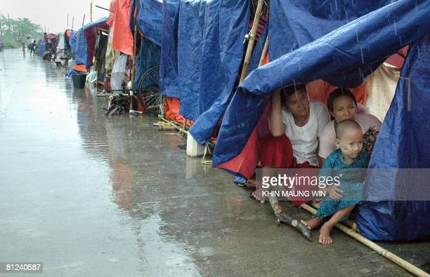 This photo taken on May 25 2008 shows cycloneaffected families sheltered from the rain living in temporary accommodation along a road in the...