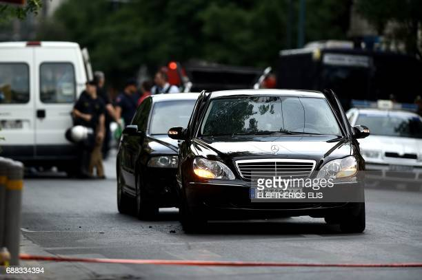 This photo taken on May 25 201 in Athens shows forensic experts of the police searching for evidence in and around the car of Greek former prime...