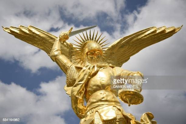 This photo taken on May 25 2016 in Mont SaintMichel shows the statue of the Archangel Michael regilded and restored with a new lighting rod on the...