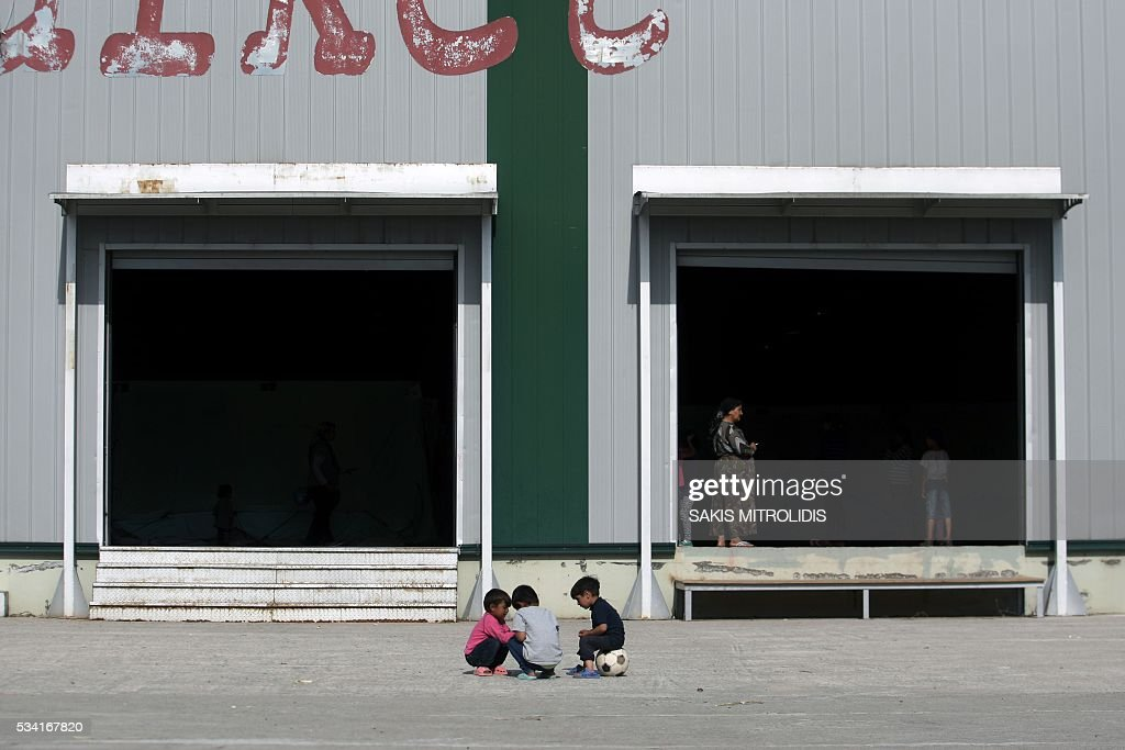 This photo taken on May 25, 2016 shows migrants and refugees within the Kalohori refugee camp, near Thessaloniki. Greek police on May 25 moved hundreds more migrants out of Idomeni, the squalid tent city where thousands fleeing war and poverty have lived for months, on the second day of an operation likely to last a week. Some 600 people were bussed away from the camp on the Macedonian border to newly opened camps near Greece's second city Thessaloniki, about 80 kilometres (50 miles) south, bringing the total moved out to 2,600 since May 24. MITROLIDIS
