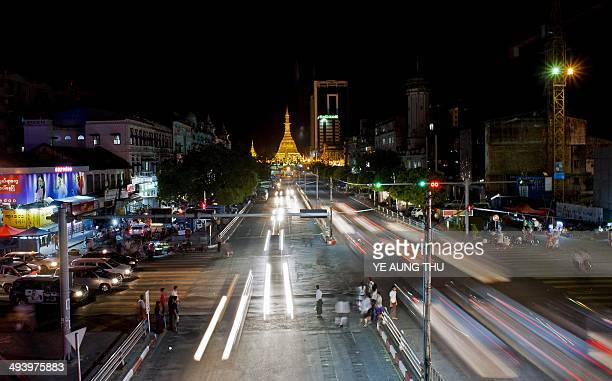 This photo taken on May 26 2014 shows commuters crossing a busy street at night in Yangon Myanmar on May 16 shrugged off US President Barack Obama's...