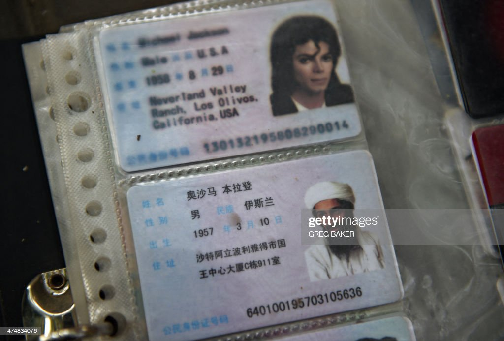 This photo taken on May 26 2015 shows imitation Chinese identification cards featuring Osama bin Laden and Michael Jackson for sale on a sidewalk in...