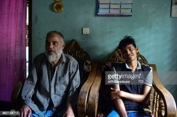 This photo taken on May 27 2017 shows teenager Khaled Hossain and his father talking to AFP during an interview with AFP in his house in Beanibazer...