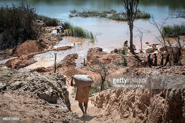 This photo taken on May 31 2015 near a mine between Lubumbashi and Kolwezi shows a man carrying a bag of minerals as people separate cobalt from sand...