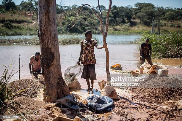This photo taken on May 31 2015 near a mine between Lubumbashi and Kolwezi shows a woman and men separating cobalt from mud and rocks one of 130000...