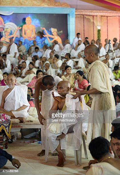 This photo taken on May 31 2015 shows millionaire Indian businessman Bhawarlal Doshi being guided by senior monks as takes blessing from a religious...