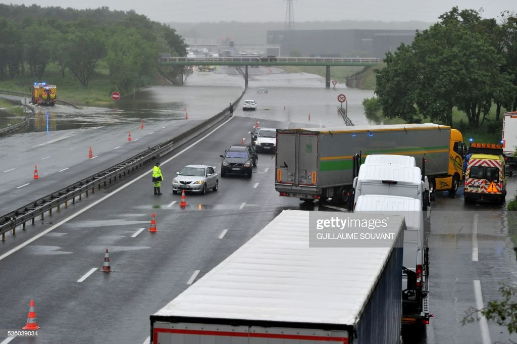 This photo taken on May 31, 2016 in Saran shows cars and lorries exiting the A10 highway, flooded due to heavy rainfall. The Loiret department is under red flood alert and France's weather agency Meteo France maintained today 18 departments are under orange alert. / AFP / GUILLAUME