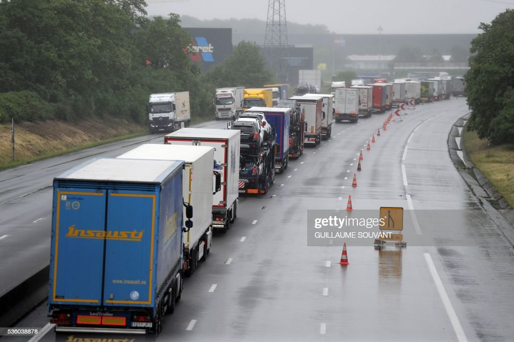 This photo taken on May 31, 2016 shows a line of lorries blocked on the A10 highway in Saran, due to heavy flooding. The Loiret department is under red flood alert and France's weather agency Meteo France maintained today 18 departments are under orange alert. / AFP / GUILLAUME