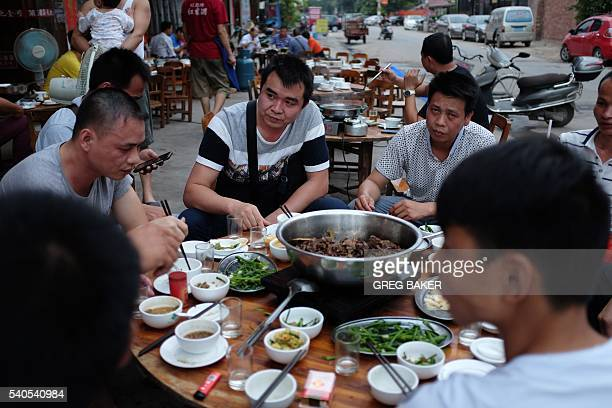 This photo taken on May 9 2016 shows people eating dog meat at a restaurant in Yulin in China's southern Guangxi region International groups and...