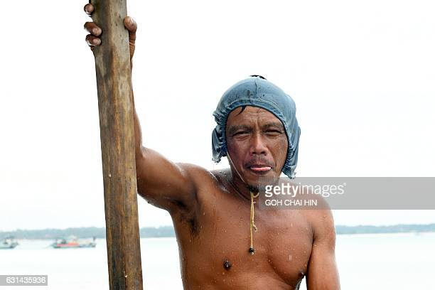 This photo taken on November 10 2016 shows illegal miner Paci after a dive where he dredged for tin from the seabed off Sungai Liat in northeast...