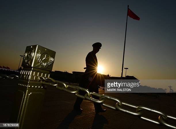 This photo taken on November 12 2013 shows a Chinese paramilitary officer patrolling Tiananmen Square in front of the Great Hall of the People after...