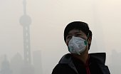 This photo taken on November 12 2014 shows a man wearing a mask amid heavy smog on the Bund in Shanghai as local meteorological department issued a...