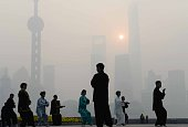 This photo taken on November 12 2014 shows residents exercising amid heavy smog on the Bund in Shanghai as local meteorological department issued a...