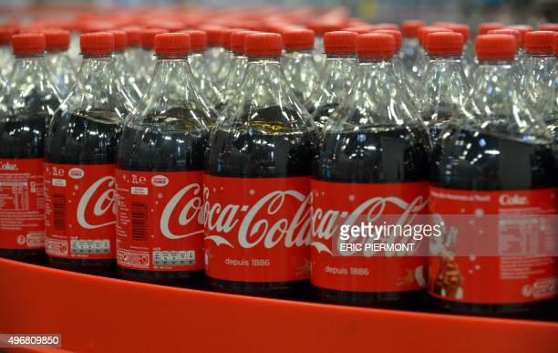 This photo taken on November 12 2015 in Grigny near Paris shows CocaCola soft drink bottles on the new assembly line at a CocaCola Entreprise...