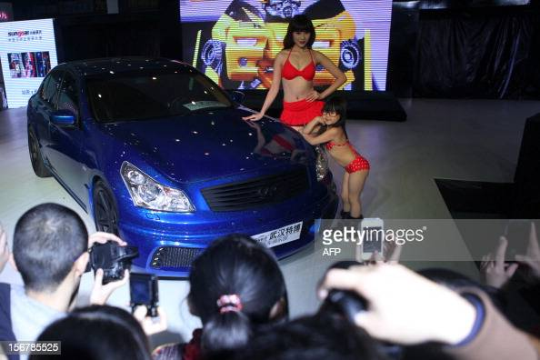This photo taken on November 16 2012 show a young child wearing a bikini and a model posing beside a car during the Chutian Auto Culture Festival in...