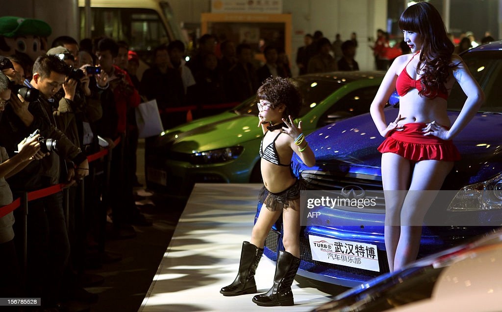 This photo taken on November 16, 2012 show a young child (C) wearing a bikini and a model posing beside a car during the Chutian Auto Culture Festival in Wuhan, central China's Hubei province. A company that featured bikini-clad child models as young as five years old at a Chinese car show sought on November 21 to defuse the controversy but also defended its actions. Many Chinese expressed outrage at the photos posted online that showed girls wearing high boots and swaying their hips in front of gleaming sedans at a car show last week in the central city of Wuhan. CHINA OUT AFP PHOTO