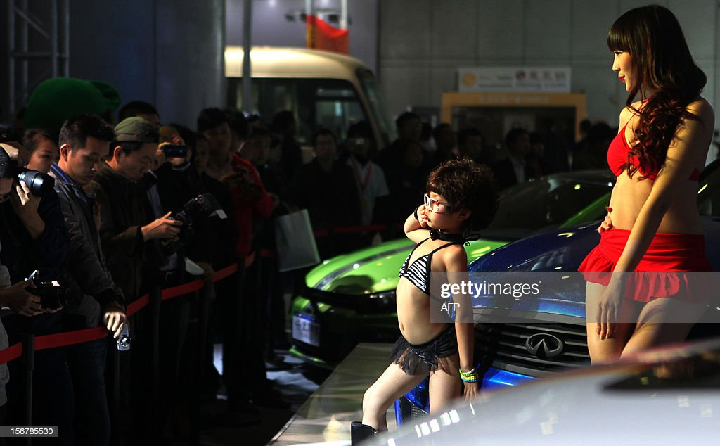 This photo taken on November 16, 2012 show a young child (C) wearing a bikini and a model posing beside a car during the Chutian Auto Culture Festival in Wuhan, central China's Hubei province. A company that featured bikini-clad child models as young as five years old at a Chinese car show sought on November 21 to defuse the controversy but also defended its actions. Many Chinese expressed outrage at the photos posted online that showed girls wearing high boots and swaying their hips in front of gleaming sedans at a car show last week in the central city of Wuhan. CHINA