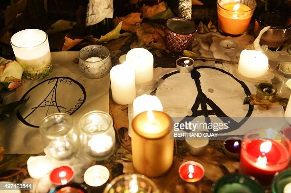 This photo taken on November 16 2015 shows candles and messages left at a makeshift memorial next to the Bataclan concert hall in Paris Islamic State...